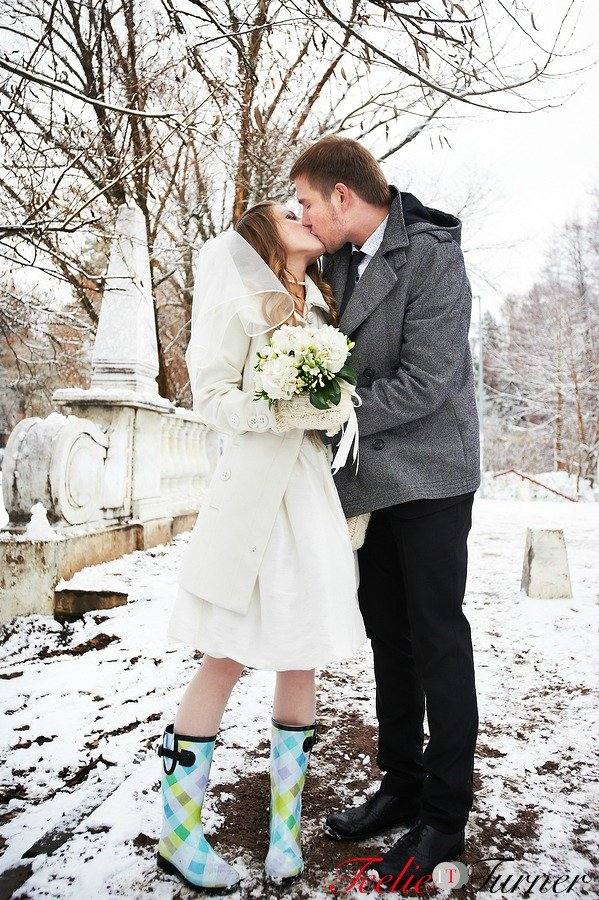 Kiss bride and groom in winter landscape on wedding day