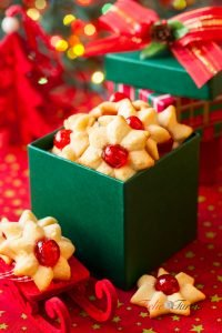 Christmas cookies with red candied cherries in the green gift bo