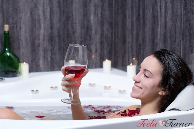 Beautiful woman in bath with rose petals drinking wine