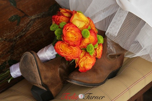 Bride is wearing cowboy boots and the bouquet is beside her boots.
