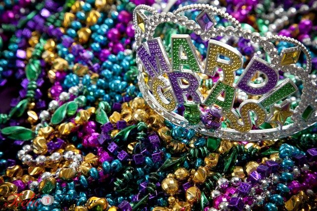 A colorful mardi gras crown or tiara lying on top of beads holiday theme