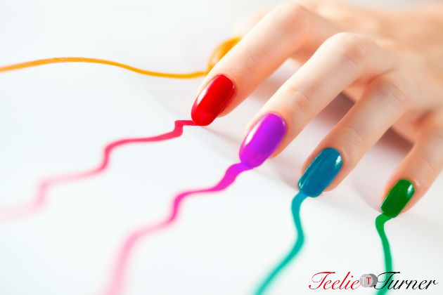 Young woman hand with multicoloured nails. On white.